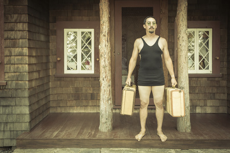dapper: Goofy Gentleman Dressed in 1920's Era Swimsuit Holding Suitcases on Porch of Cabin.