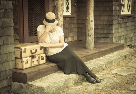 distressed: Distressed 1920s Dressed Girl Next To Suitcases on Porch with Vintage Effect Added.