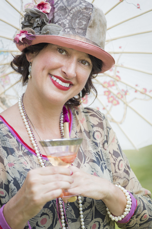 attractive  female: Beautiful 1920s Dressed Girl with Parasol and Glass of Wine Portrait. Stock Photo