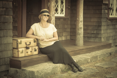 Pretty 1920s Dressed Girl Next To Suitcases on Porch with Vintage Effect Added. Stock fotó