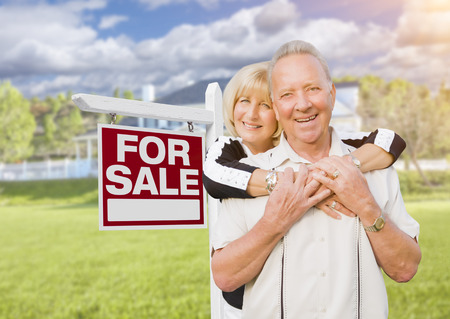 selling house: Happy Senior Couple Front of For Sale Real Estate Sign and House.