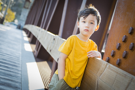 mixed race boy: Handsome Mixed Race Boy Leaning on Bridge Outdoors.