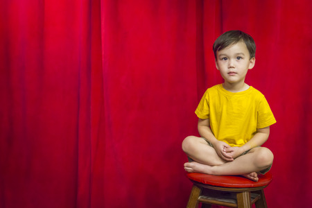 legs folded: Handsome Mixed Race Boy Sitting on Stool in Front of Red Curtain.