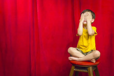 indian style sitting: Mixed Race Boy Boy Covering His Eyes Sitting on Stool in Front of Red Curtain. Stock Photo