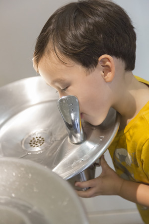 Mixed Race Boy Drinking From the Fresh Water Fountain.