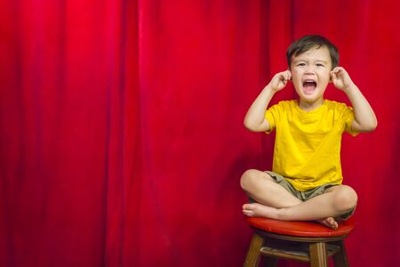 fingers: Mixed Race Boy With His Fingers In His Ears Sitting on Stool in Front of Red Curtain.