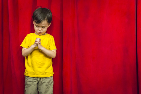 Mixed Race Boy with Praying Hands in Front of Red Curtain.