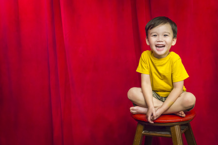 indian style sitting: Laughing Mixed Race Boy Sitting on Stool in Front of Red Curtain.