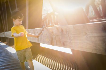 mixed race boy: Handsome Mixed Race Boy Walking on Bridge Outdoors.