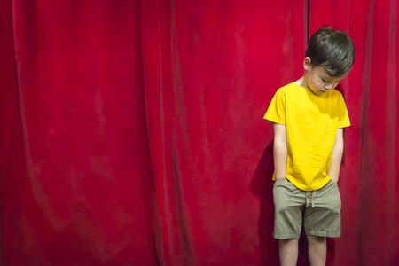 赤いカーテンの前にレースの少年立ってを混合悲しいふくれっ面。