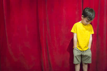 bashful: Sad Pouting Mixed Race Boy Standing In Front of Red Curtain. Stock Photo