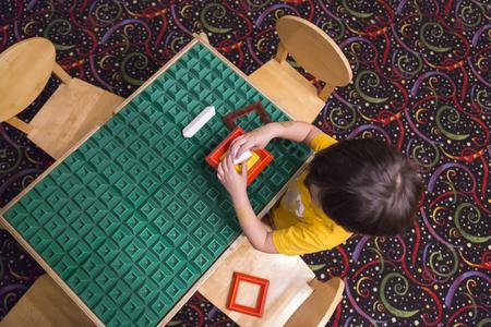 desorden: Arriba de raza mixta Muchacho que se sienta en una mesa de trabajo juega con los bloques de construcción Juguetes.