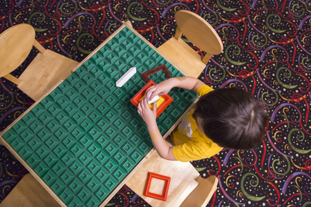 overhead: Overhead of Mixed-race Boy Sitting at a Work Table Playing with Building Blocks Toys.