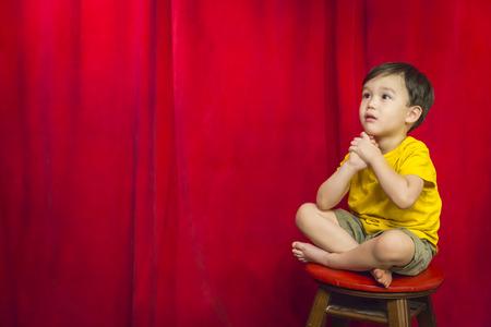 niños pensando: Muchacho hermoso mixta se sienta en taburete delante de la cortina roja. Foto de archivo