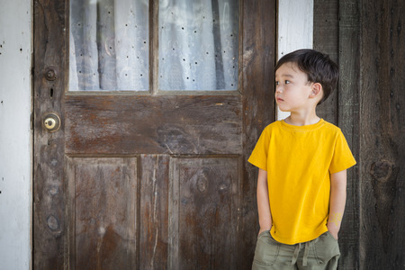 boy alone: Melancholy Mixed Race Boy Standing In Front of Door on Porch. Stock Photo
