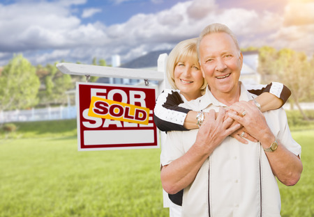 home sale: Happy Affectionate Senior Couple Hugging in Front of Sold Real Estate Sign and House. Stock Photo