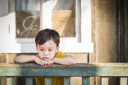 Melancholy gemischter Abstammung Junge lehnt am Geländer Veranda.
