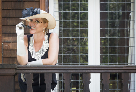 twenties: Attractive Young Woman in Twenties Outfit on Porch of an Antique House.