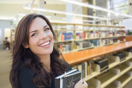 mixed race: Happy Mixed Race Girl With Books in the Library.