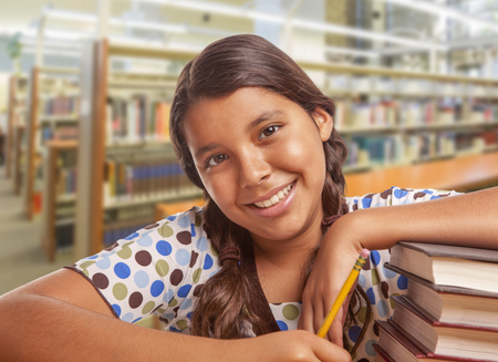 beautiful teen girl: Happy Hispanic Girl Student with Pencil and Books Studying in Library.