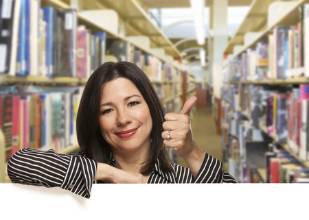 Pretty Hispanic Woman with Thumbs Up Leaning On White Board in the Library. Banque d'images
