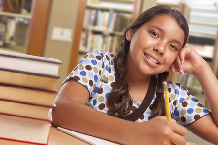 Gelukkige Spaanse Girl Student met Potlood en boeken in bibliotheek bestuderen.
