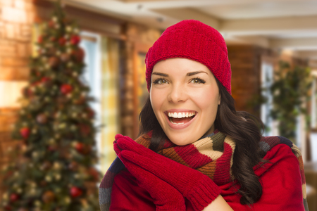 mexican girl: Happy Mixed Race Woman Wearing Mittens and Hat In Christmas Setting.
