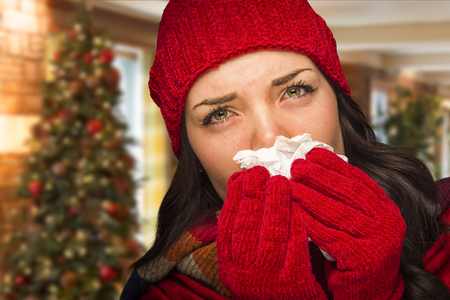 female christmas: Sick Mixed Race Woman Blowing Her Sore Nose With Tissue In Christmas Setting.
