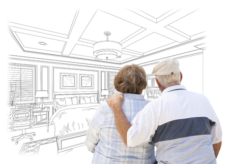 the elderly residence: Curious Senior Couple Looking Over Custom Bedroom Design Drawing.