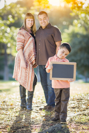 chalk board: Young Mixed Race Couple Stands Behind Son with Blank Chalk Board Outdoors.