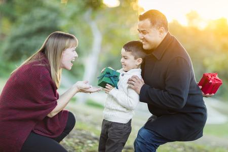 mama e hijo: Feliz joven Entrega de Regalos Hijo descendencia mixta a su mamá Como Padre Stands Atrás.