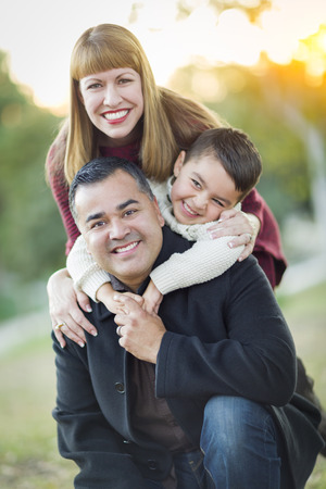 family with three children: Happy Attractive Young Mixed Race Family Portrait Outdoors.