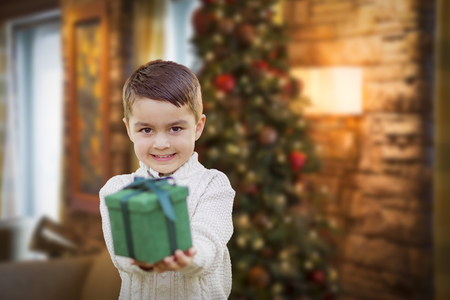 christmas present: Young Mixed Race Boy Handing Gift Out Front with Christmas Tree Behind.
