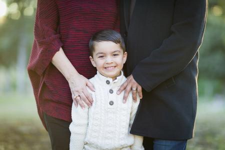 mama e hijo: Hermoso Joven Mixed Race Boy Retrato al aire libre con los padres detrás. Foto de archivo