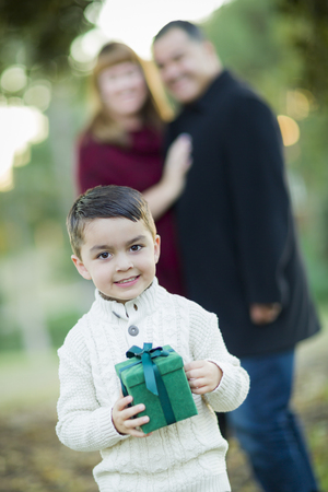 mixed race boy: Young Mixed Race Boy Holding Gift In Front with Parents Behind. Stock Photo