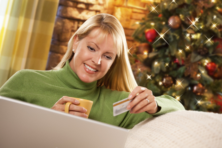 mid thirties: Beautiful Woman Using Her Credit Card In Front of Christmas Tree and Laptop Computer. Stock Photo