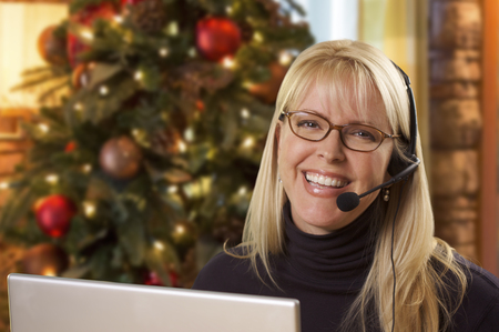 Happy Woman with Phone Headset In Front of Christmas Tree and Computer Screen.