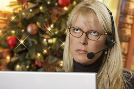 dullness: Upset Woman with Phone Headset In Front of Christmas Tree and Computer Screen. Stock Photo