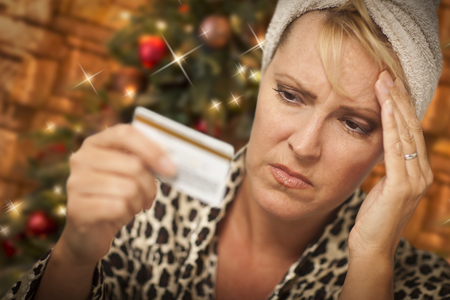 christmas debt: Very Upset Woman Holding Credit Card In Front of Christmas Tree.