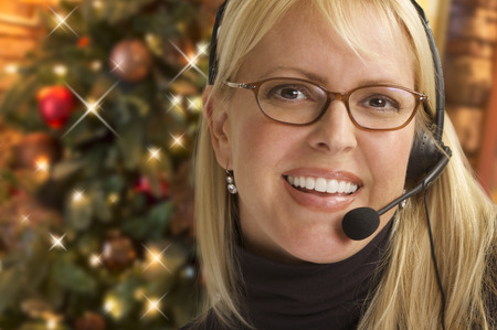 contact center: Happy Woman with Phone Headset In Front of Christmas Tree.