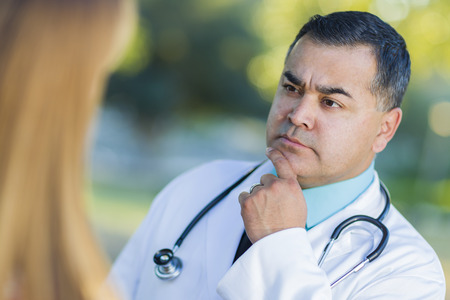 labcoat: Hispanic Male Doctor or Nurse Talking With a Patient Outdoors.