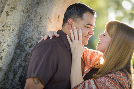 mixed race couple: Happy Mixed Race Couple Leaning Against A Tree In a Romantic Moment.