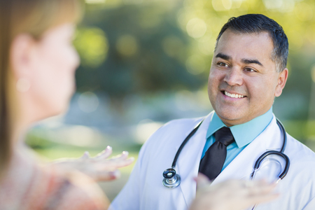 Hispanic Male Doctor or Nurse Talking With a Patient Outdoors.