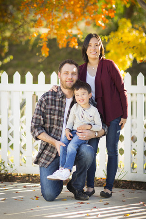 mixed race family: Happy Attractive Mixed Race Young Family Portrait Outdoors. Stock Photo