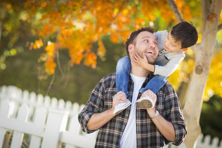 ピギーバックの白人父の肩の上に乗って幸せな混血少年。 写真素材