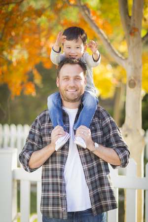 mixed race boy: Happy Mixed Race Boy Riding Piggyback on Shoulders of Caucasian Father.