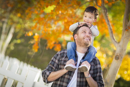 mixed race: Happy Mixed Race Boy Riding Piggyback on Shoulders of Caucasian Father.