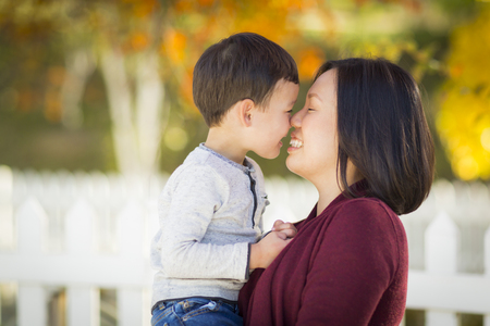 momma: Happy Chinese Mom Having Fun and Holding Her Mixed Race Little Boy. Stock Photo
