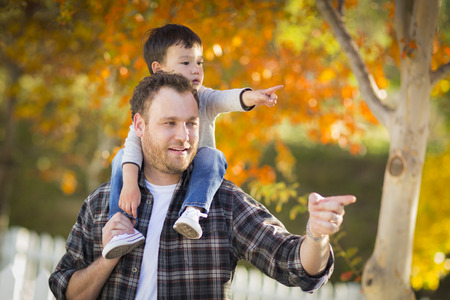 Happy Mixed Race Boy Riding Piggyback and Pointing on Shoulders of Caucasian Father.