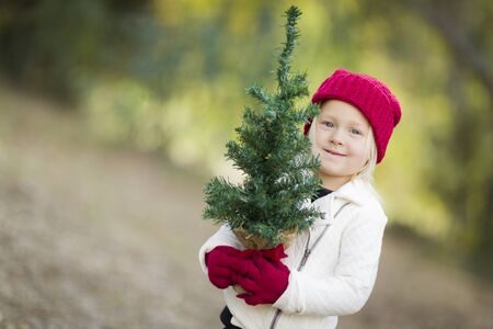 red gloves: Baby Girl In Red Mittens and Cap Holding Small Christmas Tree Outdoors.